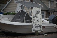 """A boat in Brick's Shore Acres section the day after Superstorm Sandy struck with a message, """"We Will Fish Again,"""" attached. (Photo: Daniel Nee)"""
