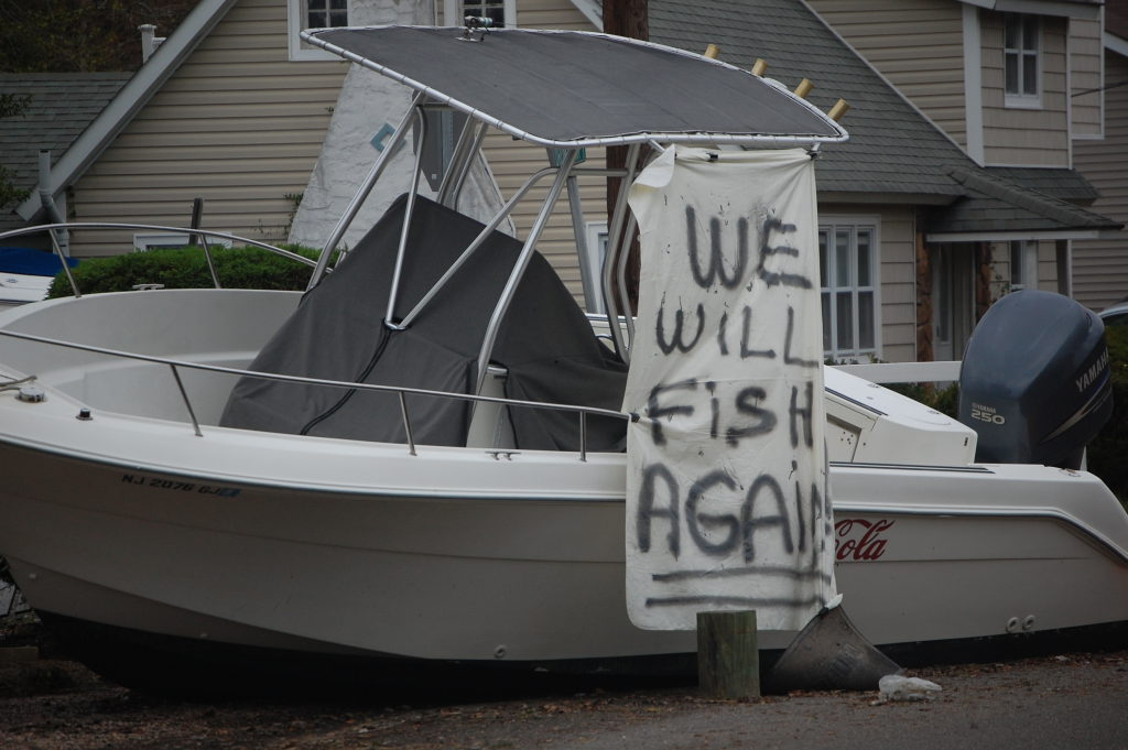 "A boat in Brick's Shore Acres section the day after Superstorm Sandy struck with a message, ""We Will Fish Again,"" attached. (Photo: Daniel Nee)"