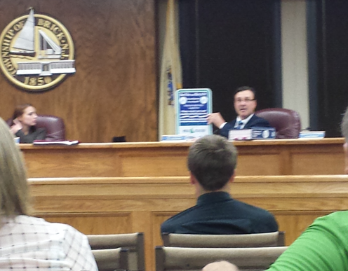 Councilman Jim Fozman holds up a sign that will be posted near fishing line recycling receptacles.