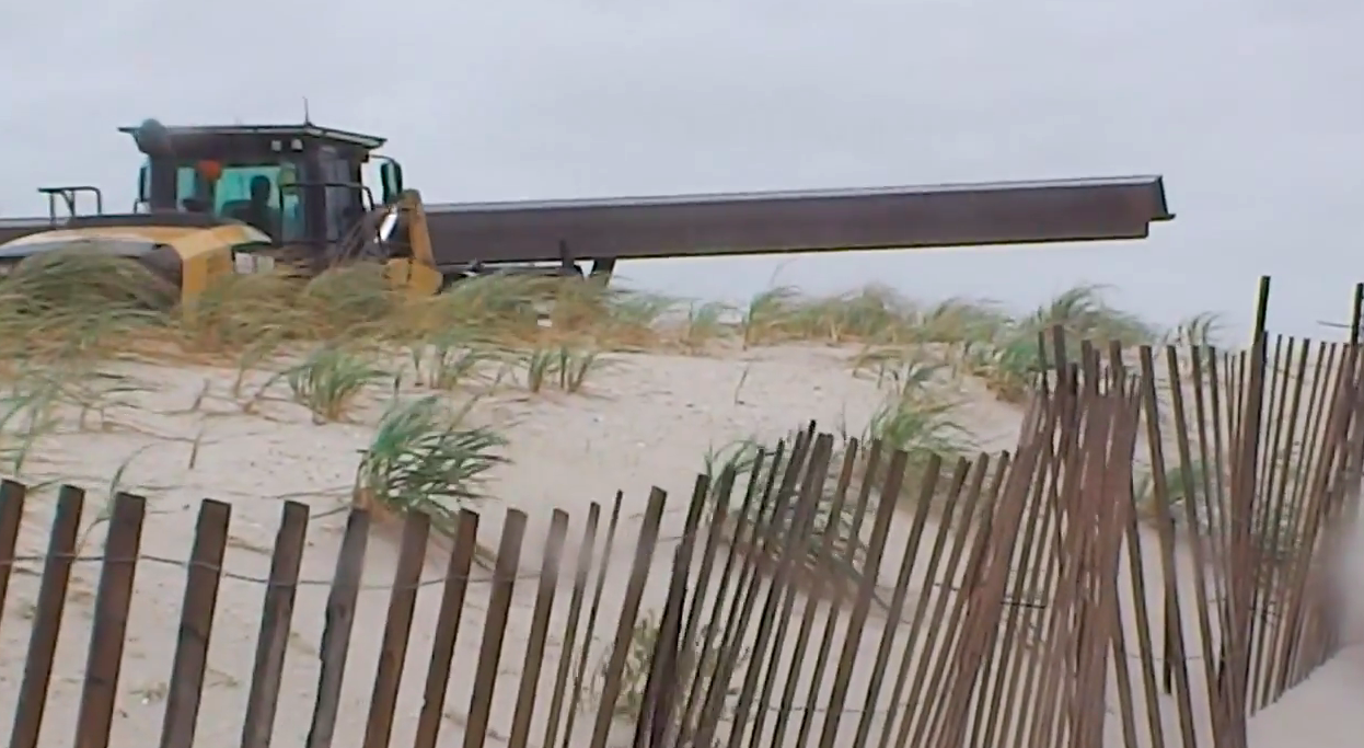 A front loader carries a steel sheet pile along Brick Beach III during a nor'easter, Oct. 22, 2014. (Video: Daniel Nee)