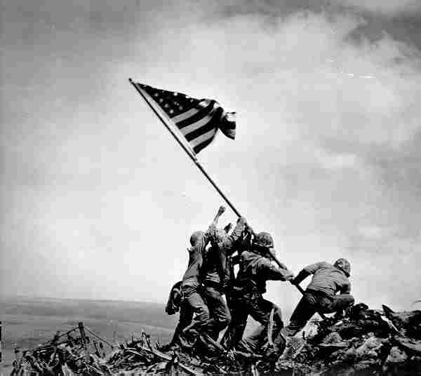 Marines and one Navy sailor raise the American flag at Mt. Suribachi. (File Photo)