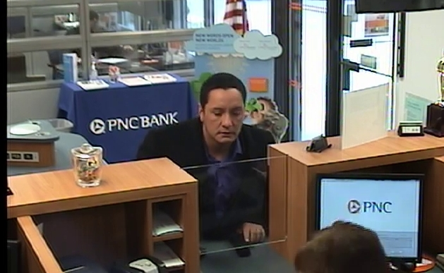 The suspect in a Feb. 5 bank robbery pulls a gun on a bank teller in Toms River. (Photo: TRPD)