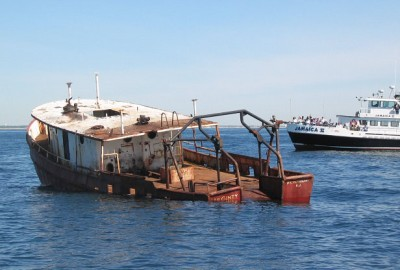 The deployment of a barge to make up an artificial reef off Manasquan Inlet. (Photo: NJDEP)