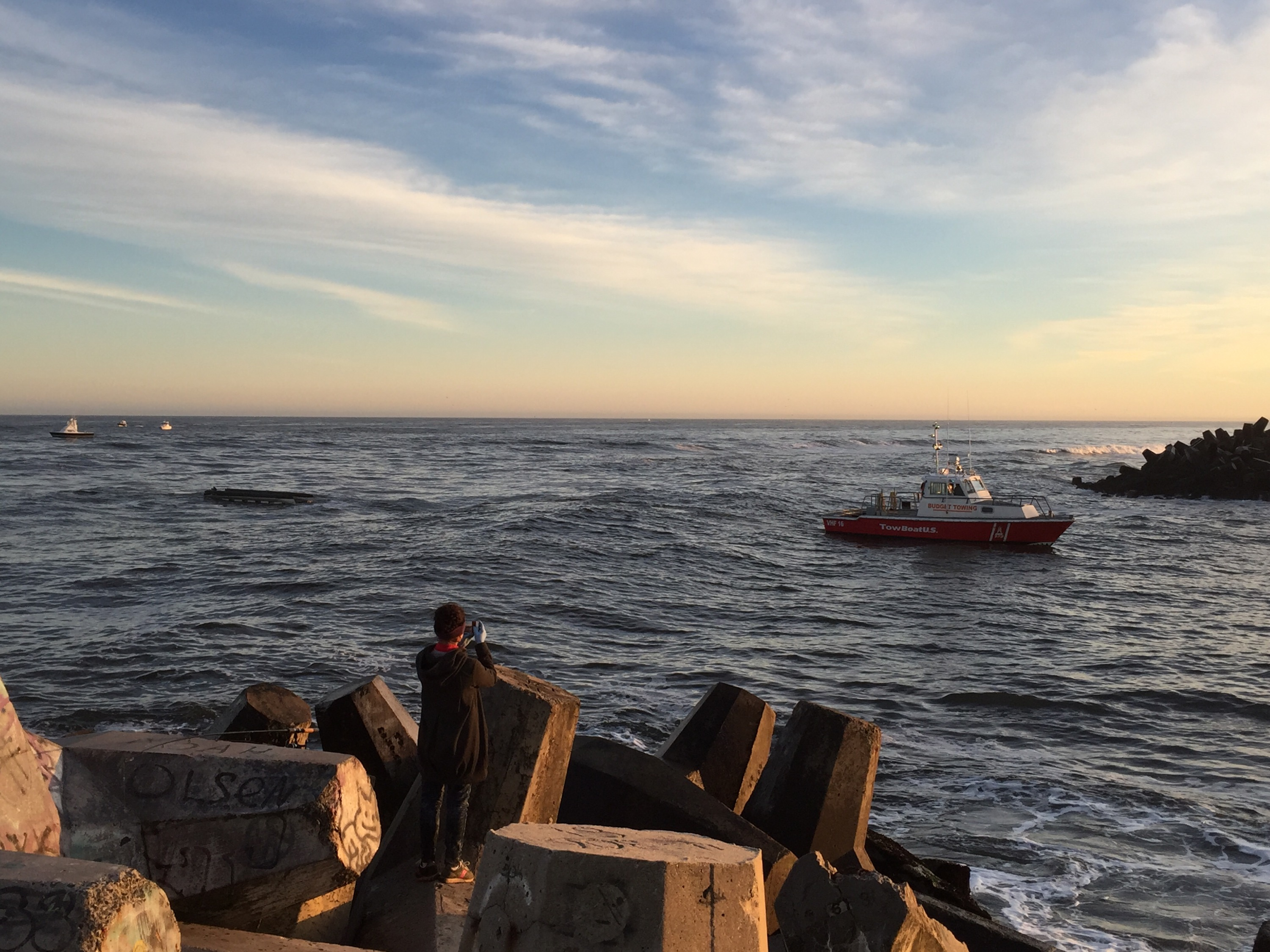 A pontoon boat that capsized off Manasquan Inlet is towed in. (Photo: Daniel Nee)