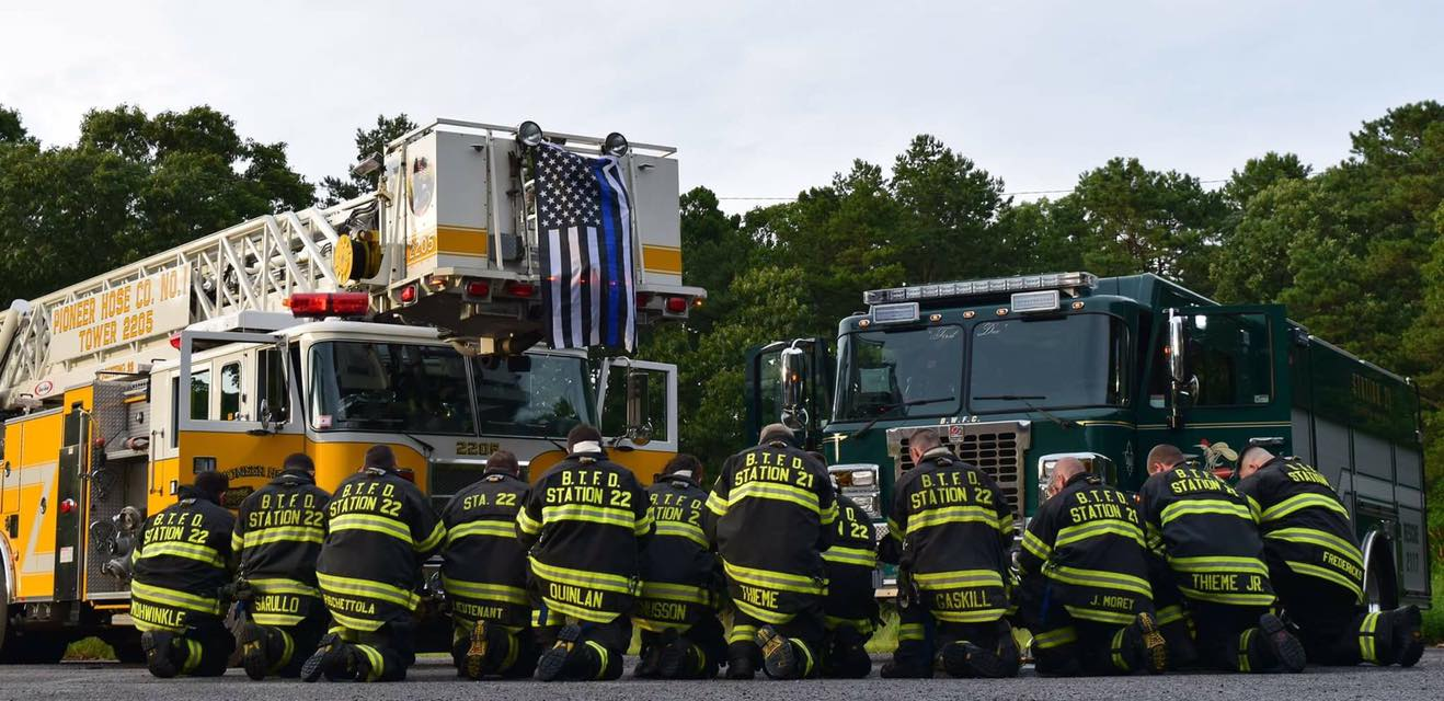 Firefighters from Brick Fire District No. 1 kneel in support of police officers. (Credit: Pioneer Hose Fire Company)