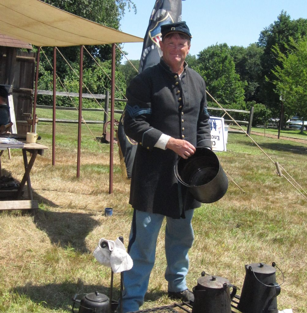 Jim Heine of Manasquan demonstrating how the soldiers cooked. (Photo: Brick Historical Society)