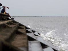 A man sits beside a levee on Lake Pontchartrain, New Orleans, La. (Credit: James Joel/ Flickr)