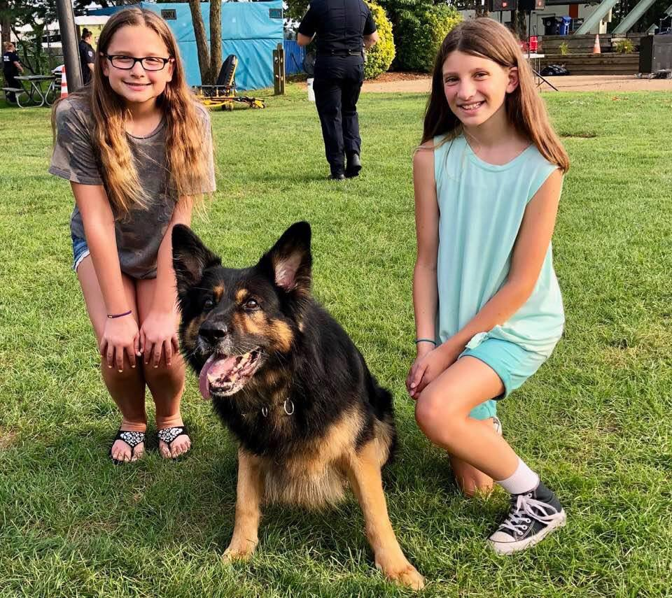 Maya Jackson and Colleen Crate with one of Brick Township's police dogs. (File Photo)