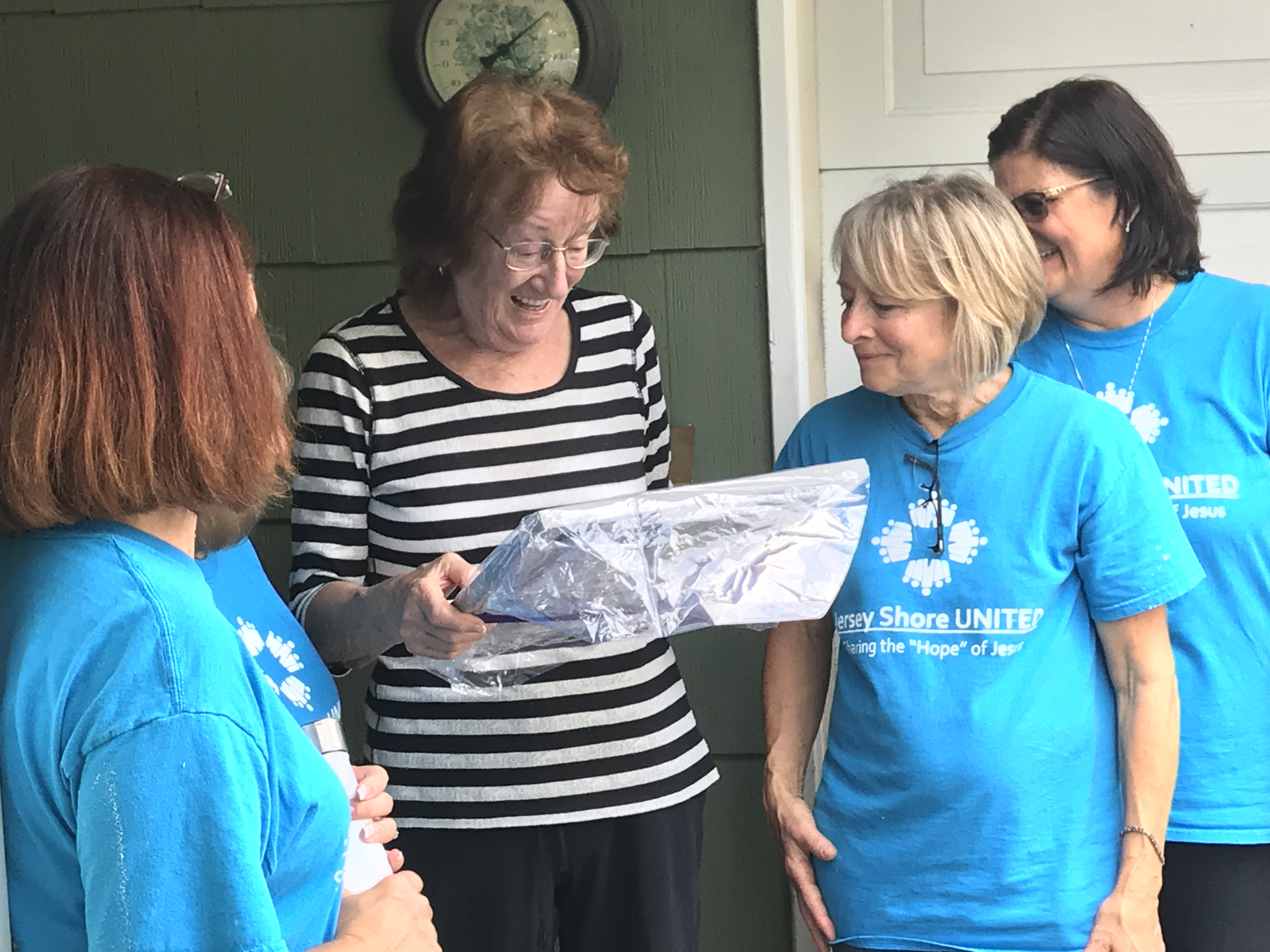 Renate Kupat receives a painting from the volunteers who helped her move back into her house in Brick's Greenbriar development, Oct. 4, 2018. (Photo: Daniel Nee)