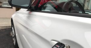 An electronic key fob next to a car door handle. (Photo: Daniel Nee)