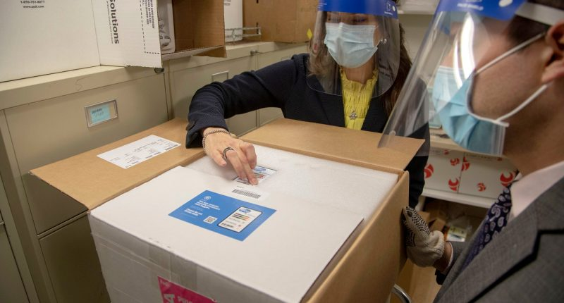 FedEx delivered the first tray of the Pfizer COVID-19 vaccine to Holy Name Medical Center in Teaneck, NJ. Nancy Palamara and Joseph Cruz accepted the vaccine and stored it in the 80 degree below zero freezer. (Credit: Jeff Rhode/Holy Name Medical Center)